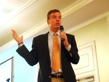 Senator Mark Warner addressing a crowded audience at the Bisnow event