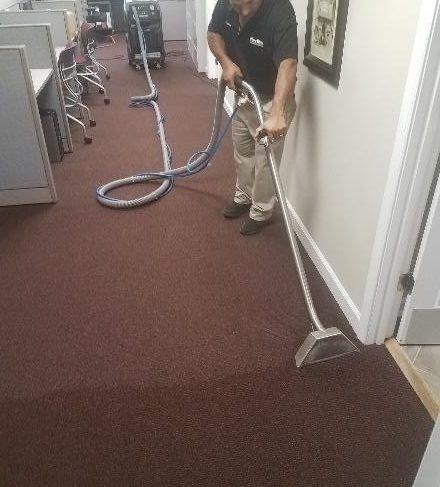 Mister Kleen employee cleaning a carpet